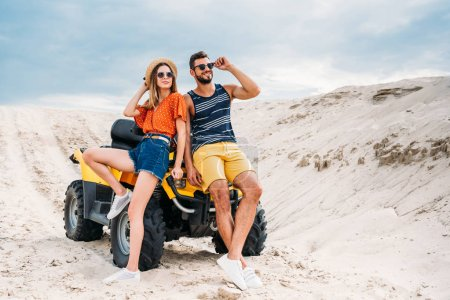 happy young couple leaning back on ATV in desert
