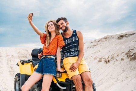 Photo pour Heureux jeune couple avec VTT prendre selfie dans le désert - image libre de droit