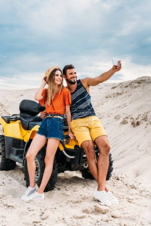 smiling young couple with ATV taking selfie in desert