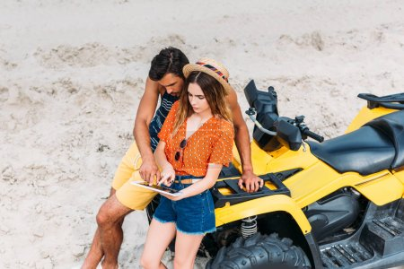 high angle view of young couple with ATV using digital tablet in desert