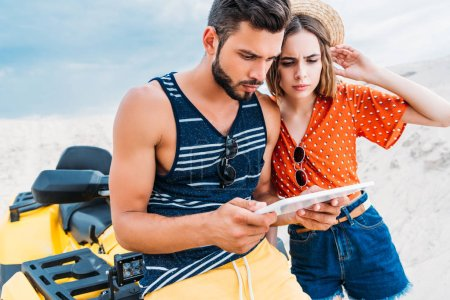 confused lost young couple with ATV using digital tablet in desert