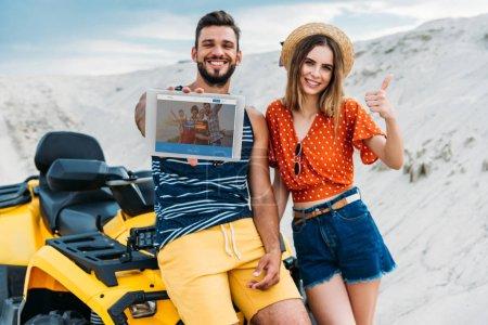 Photo pour Heureux jeune couple avec VTT montrant tablette numérique avec site de couchsurfing à l'écran et pouce vers le haut au désert - image libre de droit