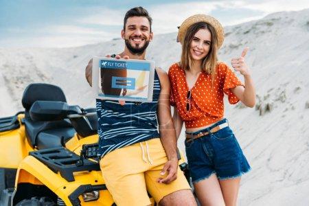 Photo pour Beau jeune couple avec VTT montrant tablette numérique avec site de réservation de billets de mouche à l'écran et pouce vers le haut au désert - image libre de droit