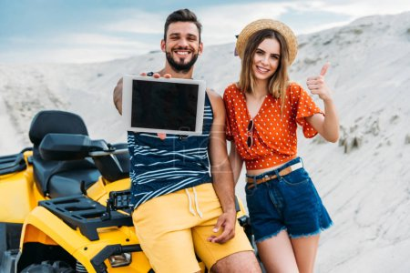 Photo pour Sourire de jeune couple avec atv montrant une tablette numérique avec écran blanc et le pouce vers le haut au désert - image libre de droit