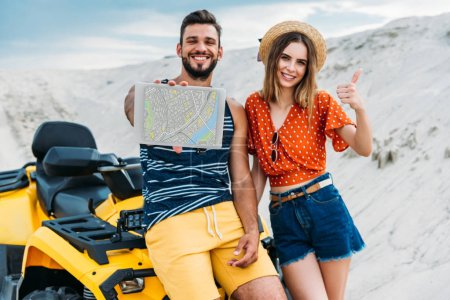 smiling young couple with atv showing digital tablet with map on screen and thumb up at desert