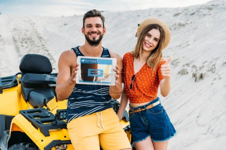 beautiful young couple with atv showing digital tablet with fly ticket booking website on screen and thumb up at desert