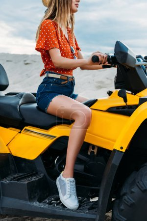 cropped shot of young woman sitting on all-terrain vehicle in desert