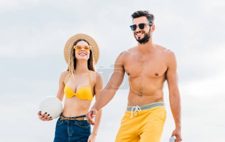 beautiful young couple in beach clothes with volleyball ball in front of cloudy sky