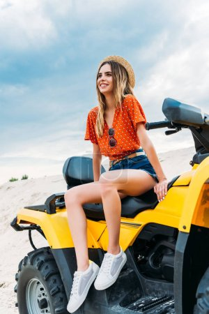 Photo pour Belle jeune femme assise sur les véhicules tout-terrain et regarder loin dans le désert - image libre de droit