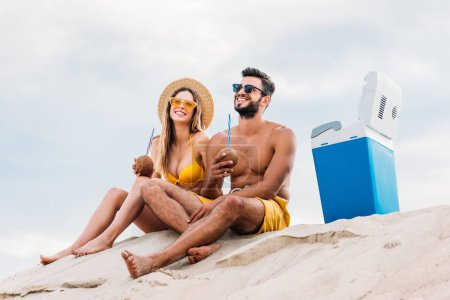 smiling young couple with coconut cocktails relaxing on sand in front of cloudy sky