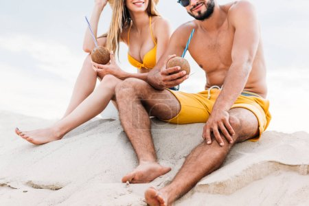 cropped shot of young couple with coconut cocktails sitting on sand in front of cloudy sky