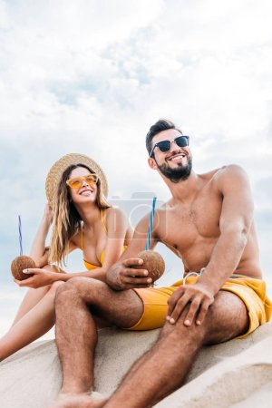 bottom view of young couple with coconut cocktails sitting on sand in front of cloudy sky