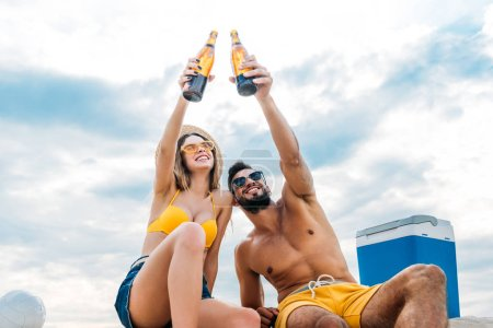 bottom view of beautiful young couple raising bottles of beer in front of cloudy sky while sitting on sand
