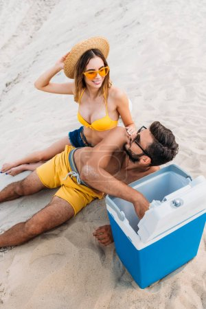 high angle view of young couple with portable fridge sitting on sand