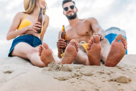 bottom view of young couple with bottles of beer sitting on sand