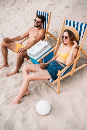 high angle view of beautiful young couple with coconut cocktails relaxing in sun loungers on sandy beach