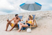 beautiful young couple with coconut cocktails relaxing in sun loungers on sandy beach