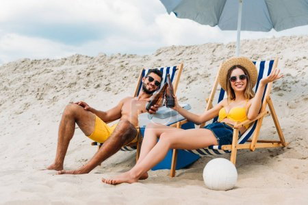 beautiful young couple with beer bottles relaxing in sun loungers on sandy beach