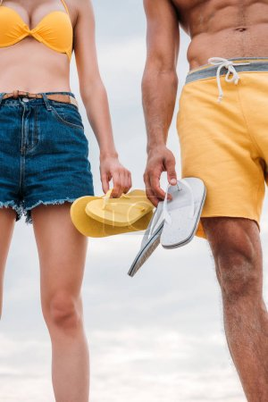 cropped shot of couple in shorts holding flip flops in front of cloudy sky