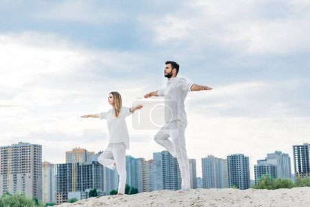 beautiful young couple practicing yoga in tree pose (Vrksasana) on sandy dune with city buildings on background