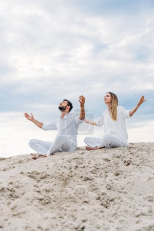 young fit couple on yogi meditating while sitting on sandy dune in lotus pose (padmasana)