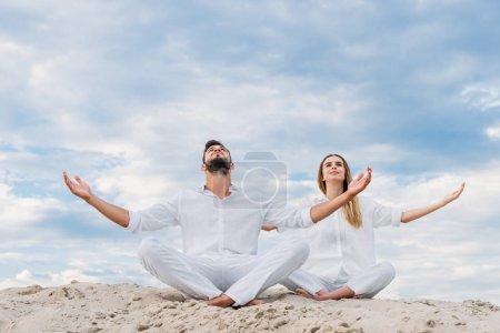 young couple on yogi meditating while sitting on sandy dune in lotus pose (padmasana)
