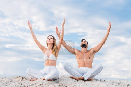 beautiful young couple sitting on sandy dune in lotus pose (padmasana) with raised arms