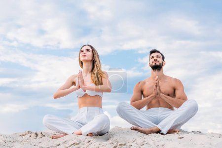 fit young couple meditating while sitting on sandy dune in lotus pose