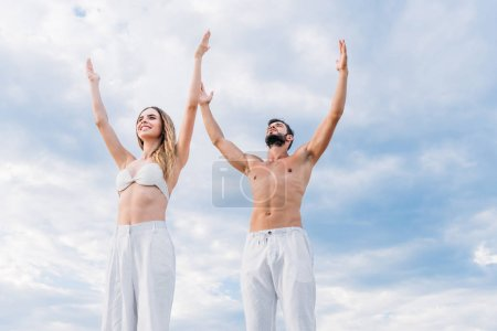 fit young couple with raised arms meditating under cloudy sky