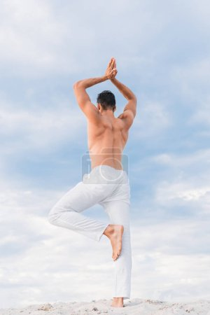 handsome young man practicing yoga in tree pose in front of cloudy sky