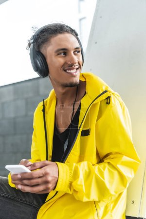 happy mixed race man in headphones listening music with smartphone and looking away at city street