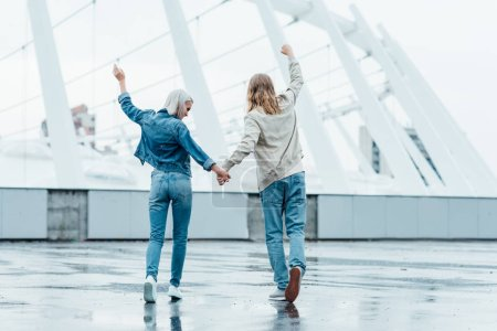 rear view of young couple holding hands and raising fists on street on cloudy day