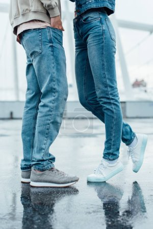 cropped shot of young couple in jeans and sneakers flirting on parking