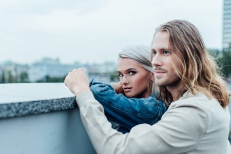Photo for Beautiful young couple standing at city viewpoint together - Royalty Free Image