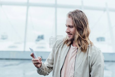 handsome young man using smartphone on street on cloudy day