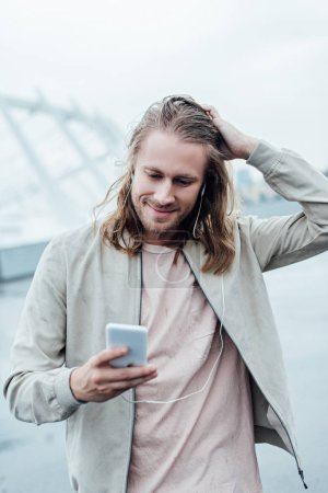 happy young man listening music with earphones and smartphone on street