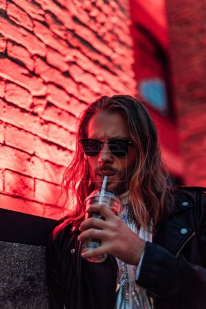 handsome young man in sunglasses and leather jacket drinking take away cocktail from plastic cup under red light on street