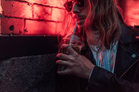 attractive young man in sunglasses and leather jacket drinking take away cocktail from plastic cup under red light on street