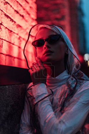 Photo for Beautiful young woman in transparent raincoat and sunglasses on street at night under red light - Royalty Free Image