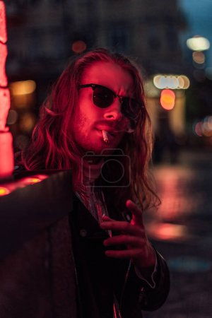 stylish young man in sunglasses smoking cigarette under red light on street
