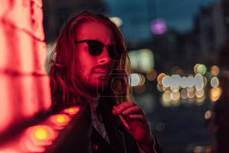attractive young man in sunglasses smoking cigarette under red light on street
