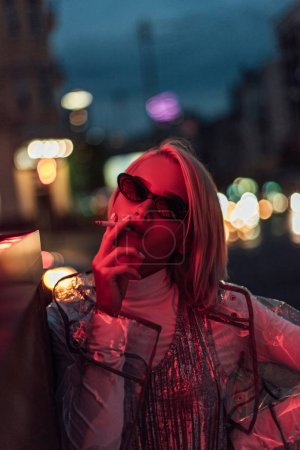 Photo for Beautiful young woman in transparent raincoat and sunglasses smoking on street at night under red light - Royalty Free Image