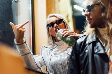 young stylish woman in sunglasses drinking mojito from plastic cup and showing middle finger at camera while spending time with boyfriend on street at night