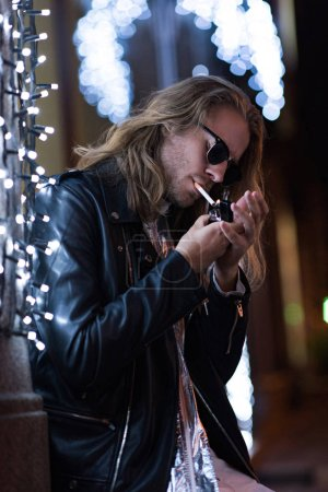 attractive young man in sunglasses and leather jacket smoking cigarette under garland on city street at night