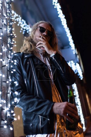 bottom view of handsome young man in sunglasses and leather jacket holding bottle of beer and smoking cigarette under garland on street at night