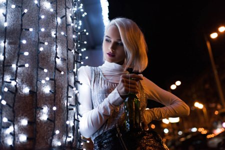 young woman with bottle of beer on street at night leaning on wall with white garland