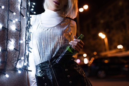cropped shot of young woman with bottle of beer on street at night leaning on wall with white garland