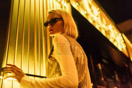 bottom view of young woman in sunglasses and glossy top over turtleneck on street at night under yellow light