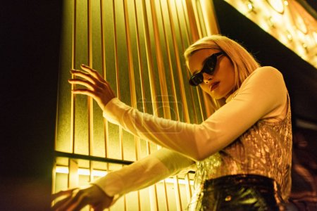 bottom view of stylish young woman in sunglasses and glossy top over turtleneck on street at night under yellow light
