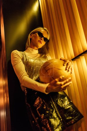 bottom view of stylish young woman in sunglasses with golden glossy basketball ball on street at night under yellow light